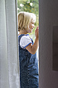 Portrait of little girl standing at the window - JFEF000450