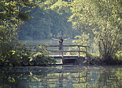 Germany, Bavaria, Young woman standing on wooden bridge at a lake - MW000058