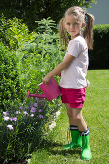 Portrait of little girl pouring plants with pink watering can in the garden - YFF000188