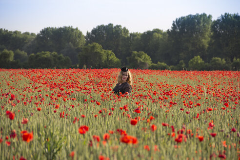 Woman wearing black cap standing in poppy field - YFF000189