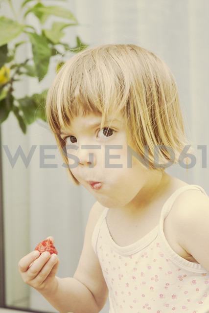 Portrait of little girl eating strawberry - LVF001486