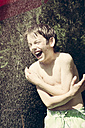 Portrait of boy taking a shower in the garden - LVF001488