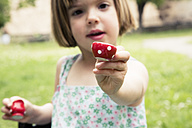 Portrait of little girl playing with doll's china set in the garden - LVF001497