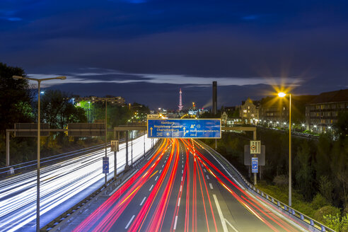 Germany, Berlin, Berlin-Charlottenburg, Federal Motorway 100 through downtown Berlin with the Funkturm Berlin in the background at night - NKF000152