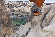 Turkey, Cappadocia, view to gondola of hot air balloon  hoovering over tuff rock formation at Goereme National Park - SIE005519