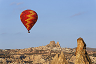 Turkey, Cappadocia, hot air balloon hoovering in front of the village Uchisar at Goereme National Park - SIEF005523