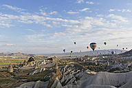 Turkey, Cappadocia, hot air balloons hoovering over tuff rock formations at Goereme National Park - SIE005528