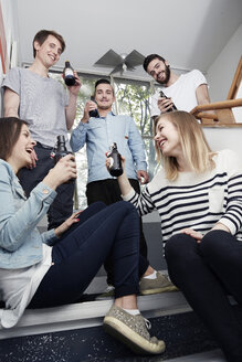 Group of creative professionals drinking beer in staircase - STKF000895
