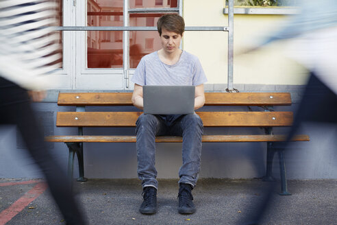 Man sitting on bench using laptop with people passing by - STKF000904