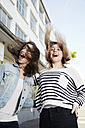 Two happy young women jumping outdoors - STKF000907