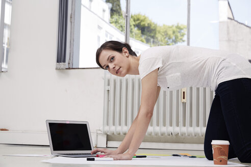 Young woman using laptop on floor - STKF000940