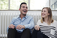 Happy man and woman sitting on floor - STKF000994