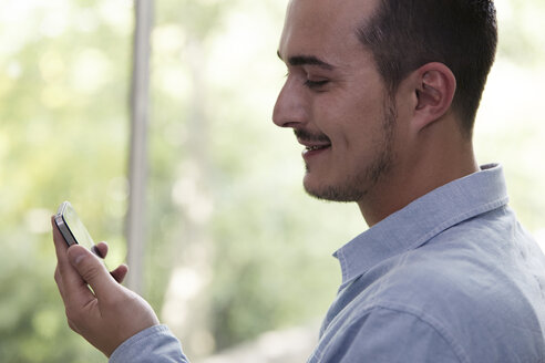 Smiling man looking at cell phone - STKF000999