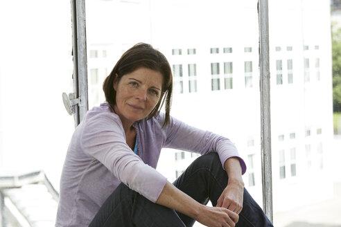 Mature woman sitting at the window - STKF001002