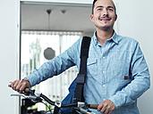 Man pushing bike in office - STKF001005