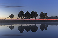 Germany, Lower Saxony, Gifhorn, Lake and reflections of trees, Road with light trail in the evening - PVCF000025