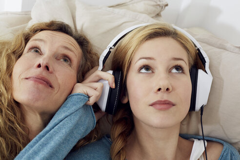 Portrait of mother and daughter listening music with headphones at home - STKF001020