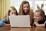 Mother and her two daughters lying on wooden floor at home using laptop - STKF001029