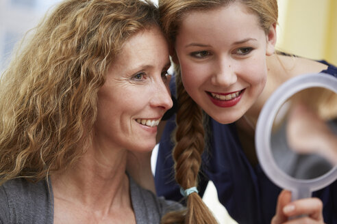 Portrait of mother and daughter looking at mirror - STKF001052