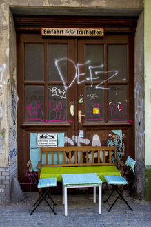 Germany, Berlin, Kreuzberg, table and chairs of street cafe standing in front of gateway - BIG000014