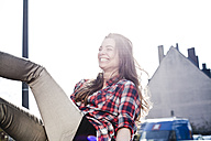 Laughing young woman having fun on a car roof - FEXF000084