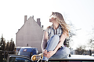 Young woman sitting on car roof - FEXF000089