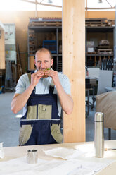 Craftsman in workshop having breakfast break - FKCF000027