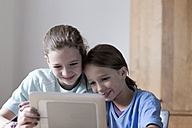 Brother and sister looking at tablet computer at home - SGF000822