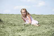 Germany, Bavaria, Young girl sitting on meadow with hay - MAEF008568