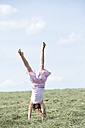 Germany, Bavaria, Young girl doing a handstand on meadow with hay - MAEF008571