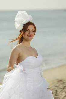 Netherlands, Texel, De Cocksdorp, woman in bridal gown at the beach - HTF000491