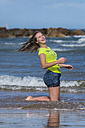 Female teenager having fun at waterside of the beach - STSF000429