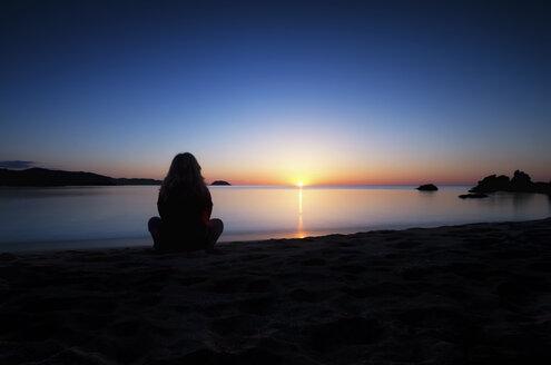 Spain, Menorca, Woman watching sunset at Playa de Cavalleria - SMAF000213