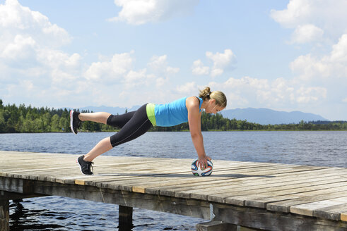 Germany, Bavaria, Sachsenkam, woman exercising functional training on jetty at sea - LHF000368