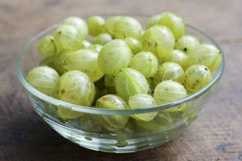 Glass bowl of gooseberries on wood, close-up - HAWF000368