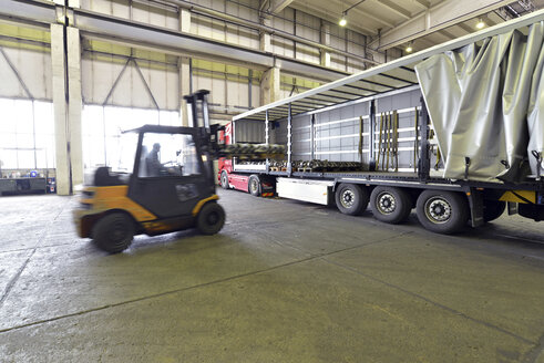 Germany, Saxony, worker driving with pallet transporter in a foundry - LY000153