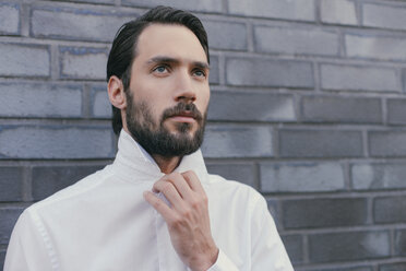 Portrait of young man folding up the collar of his shirt - MFF001144