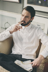 Portrait of young man smoking cigarillo - MFF001147