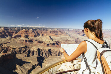 USA, Arizona, young woman with map orientating in front of Grand Canyon - MBEF001082