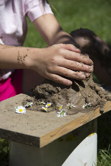Hands of little girl playing with sand in the garden - YFF000197