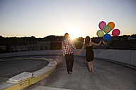 Teenage couple with balloons on parking ramp - FKF000568