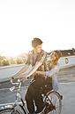 Happy teenage couple outdoors on bicycle - FKF000574