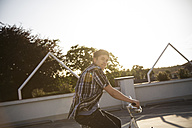 Teenage boy with bicycle on parking lot - FKF000579