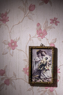 Picture frame with old photograph hanging on wallpaper with pink floral design - EJW000445