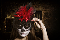 Portrait of woman with skull make-up wearing cylinder with red feather, studio-shot - STB000189