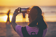 Indonesia, Bali, woman on the beach photographing sunset with her smartphone - EBSF000253