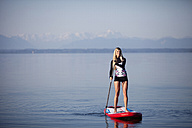 Germany, Bavaria, young woman standing on stand up paddle board at Lake Starnberg - FAF000023