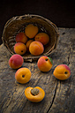Sliced and whole apricots on wood with basket at the background - LVF001535