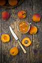 Glass of apricots jam, knife and sliced and whole apricots on wood, elevated view - LVF001537