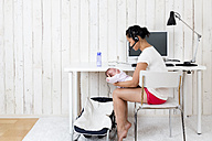 Woman at home office with her baby - DRF000941